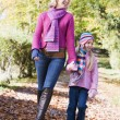 Mother and daughter walking along woodland path — Stock Photo