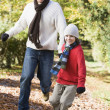Father and son running along autumn path — Stock Photo