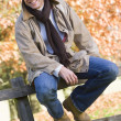 Young man sitting on fence — Stock Photo
