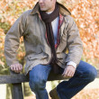 Stock Photo: Young man sitting on fence