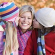 Children giving mother kiss on walk - Foto Stock