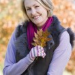 Senior woman holding autumn leaf outdoors — Stock Photo