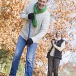 Senior couple tidying autumn leaves — Stock Photo