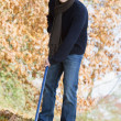 Young man clearing autumn leaves — Stock Photo