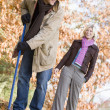 Stock Photo: Couple raking up autumn leaves
