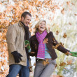 Young couple having throwing leaves in the air — Stock Photo