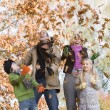 Family throwing leaves in the air — Stockfoto #4754977