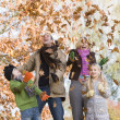 Family throwing leaves in the air — Stock Photo