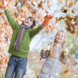 Two children throwing leaves in the air — Stock Photo #4754979