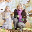 Royalty-Free Stock Photo: Mother and daughter throwing leaves in the air