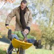 Stock Photo: Father giving son ride in wheelbarrow