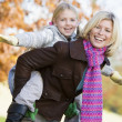 Mother giving daughter piggy back ride — Stock Photo #4754995