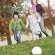 Mother and children playing football in garden — Stock Photo