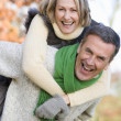 Senior man giving woman piggyback ride — Stock Photo #4754998