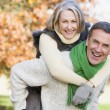 Senior man giving woman piggyback ride — Photo