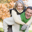 Senior man giving woman piggyback ride - Stock Photo