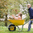 Young boy pushing girl in wheelbarrow — Stock Photo