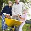 Children helping father to collect autumn leaves — Stock Photo #4755023