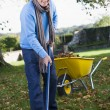 Senior man collecting leaves in garden — Stock Photo #4755034