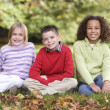 Group of children sitting in garden — Stock Photo #4755039