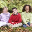 Group of children sitting in garden — Stock Photo