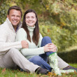 Couple sitting in autumn woods — Stock fotografie