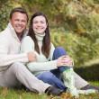 Couple sitting in autumn woods — Stock Photo