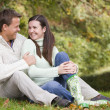 Couple relaxing in autumn woods — Stock Photo