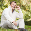 Man sitting outside in autumn landscape - Stock Photo