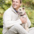 Man sitting outside holding dog — Stock Photo #4755060