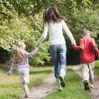Mother and children running along woodland path — Stock Photo #4755074