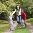 Stock Photo: Mother and children running along woodland path