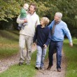 Stock Photo: Grandfather walking with son and grandchildren