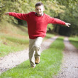 Young boy running along woodland path — Stock Photo