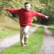Stock Photo: Young boy running along woodland path