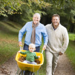 Grandfather with grandson and son pushing wheelbarrow — Stock Photo