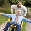 Grown up son pushing father in wheelbarrow - Stock Photo
