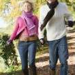 Stock Photo: Young couple running along woodland path