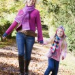 Stock Photo: Mother and daughter running along path