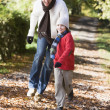Father and son running along woodland path — Stock Photo