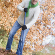 Senior man tidying leaves in garden - Stock Photo