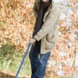 Man tidying autumn leaves — Stock Photo