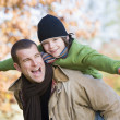 Father giving son piggyback - Stockfoto