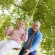 Royalty-Free Stock Photo: Grandfather pushing granddaughter on swing
