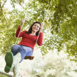 Young woman on tree swing - Stock Photo
