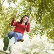 Stock Photo: Young womon tree swing