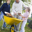Children helping father to collect autumn leaves — Stockfoto