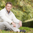 Young man sitting outside in autumn landscape — Stock Photo