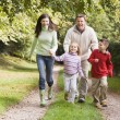 Family running along woodland track — Stock Photo