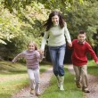 Mother and children running along woodland path — Stock Photo #4755166